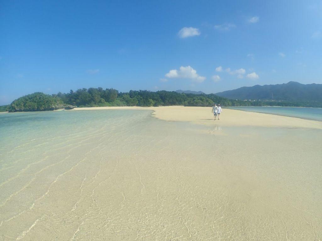 川平湾の無人島ビーチを歩くツアー客