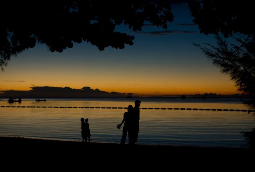 底地ビーチで夕焼け空を眺める人々